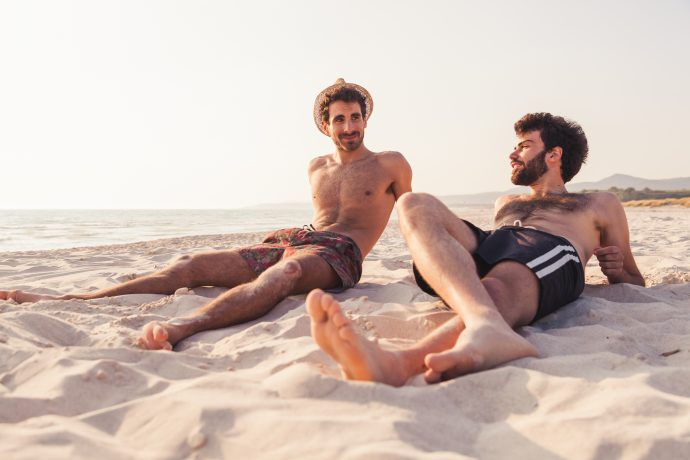 Couple of male friends at sunset on the beach